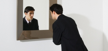 Businessman Looking in Mirror